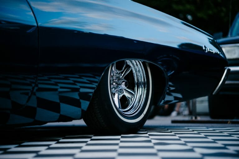 Car shipping: Receive your vehicle upon delivery. Upclose image of a wheel of a vintage car