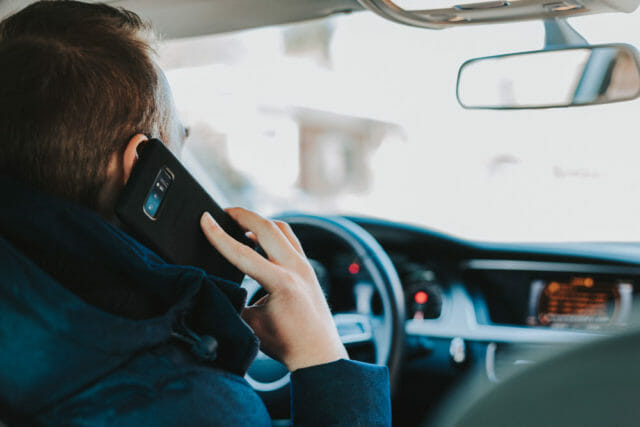 Image of man on the phone in his car