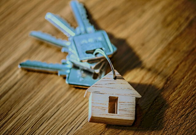 keys with a house keychain on a wooden table