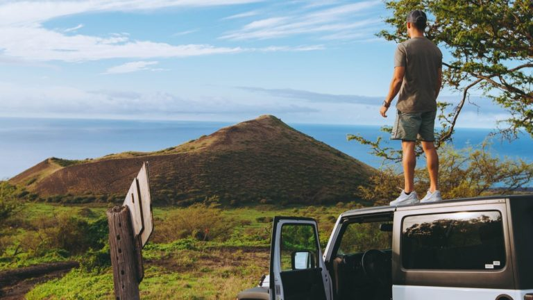 Man on top of jeep_ request a quote for car shipping to or from Hawaii