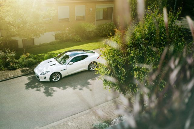 Jaguar F-Type next to a building_ship a car with a loan to or from Hawaii